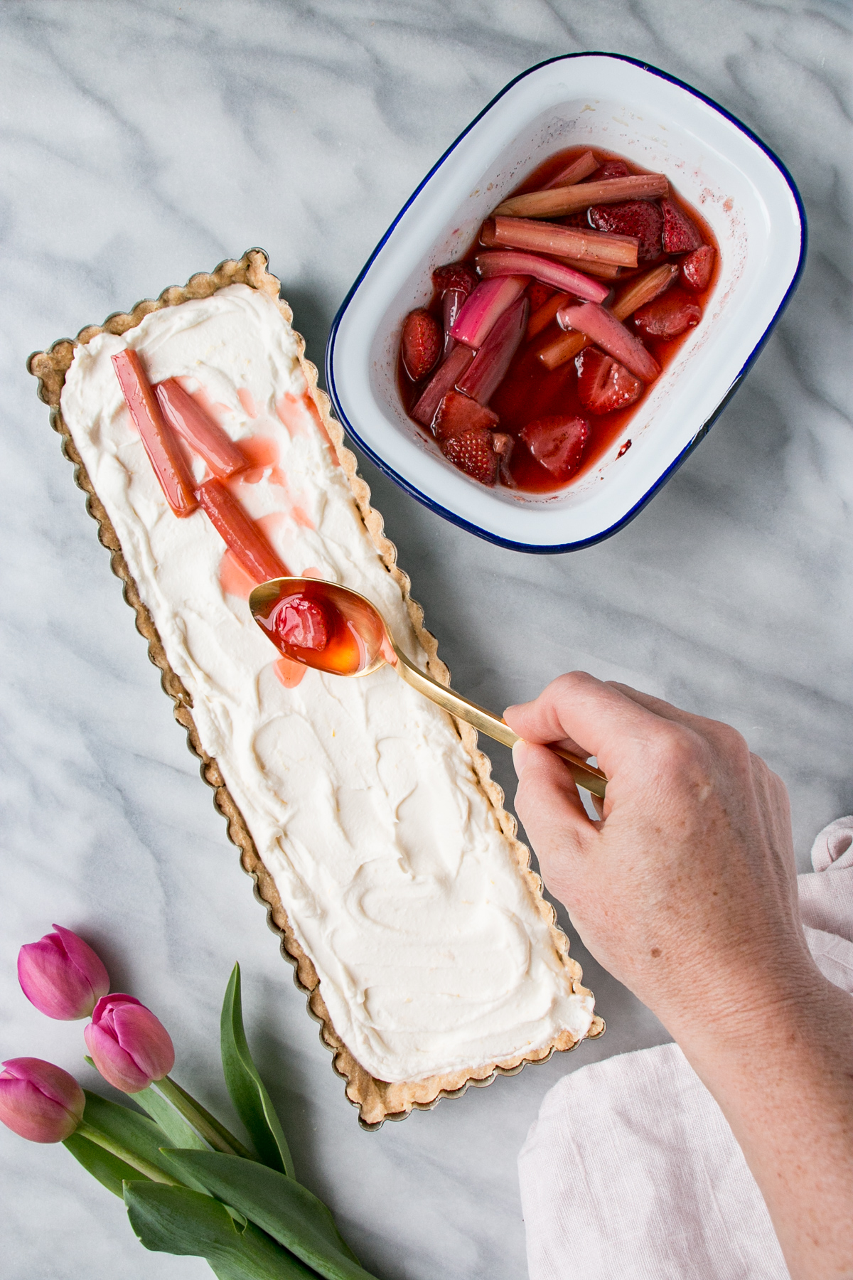 a person spooning a strawberry rhubarb mixture over a white (lemon) tart.