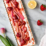 strawberry rhubarb tart with pink flowers and strawberry and lemon on the side