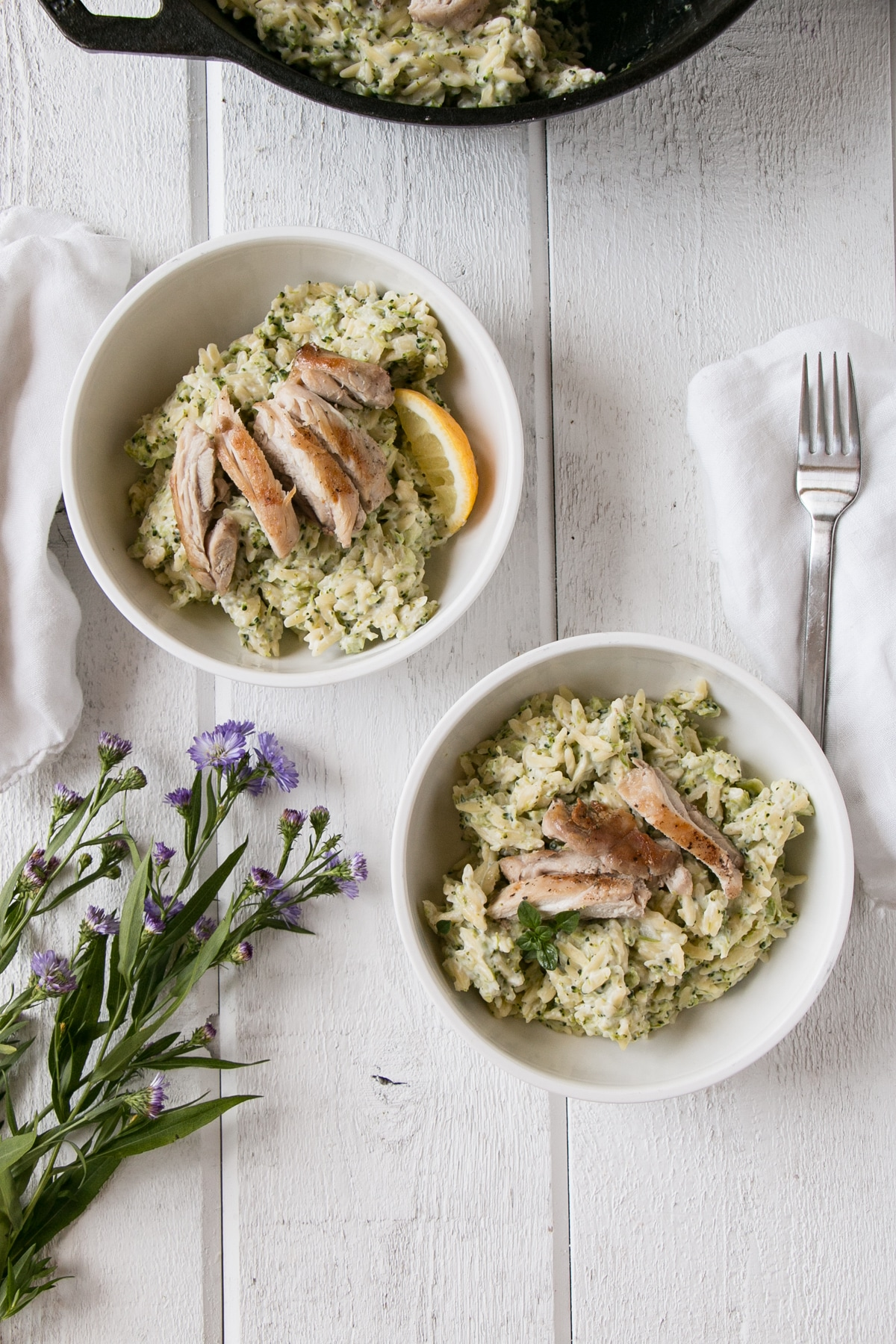 Broccoli and Goat's Cheese Orzo with chicken sliced on top in a white bowls.
