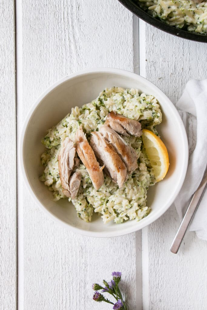 Broccoli and Goat's Cheese Orzo with chicken sliced on top in a white bowl.