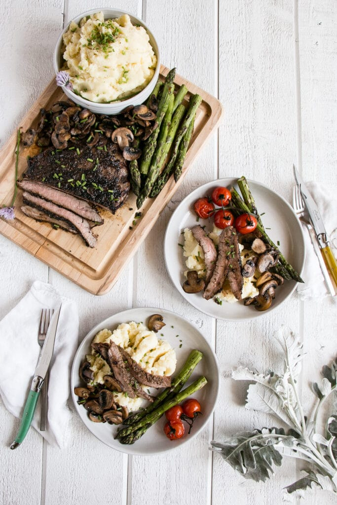 Porcini Rubbed Flank Steak on a white plate with mushrooms, asparagus and grilled cherry tomatoes