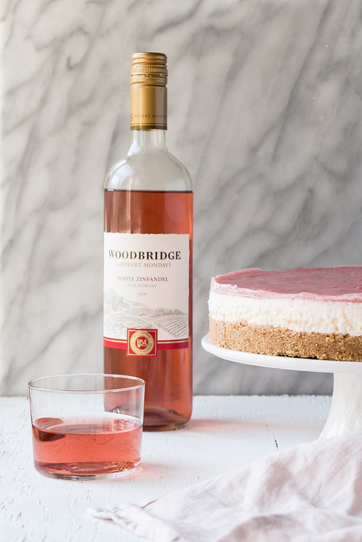 No Bake Rhubarb Cheesecake on a white cake stand with a glass and bottle of rose wine.