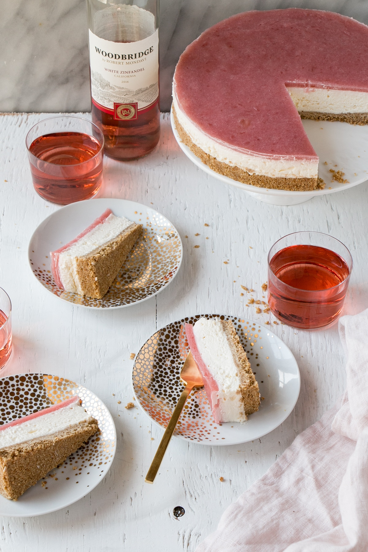 Slices of a No Bake Rhubarb Cheesecake on plates and glasses of rose wine.