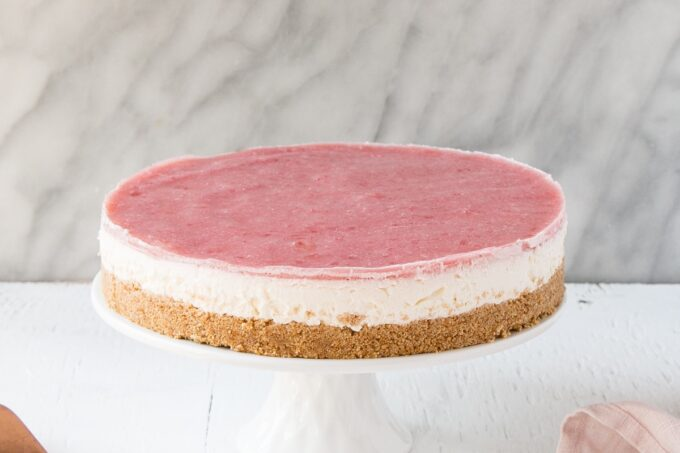 Side view a of No Bake Rhubarb Cheesecake on a white cake stand with a pink tea towel and a serving knife.