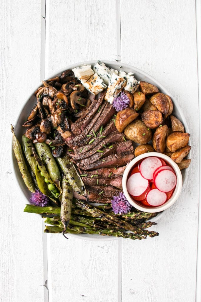 Steak (sliced), with lots of grilled vegetables, pickled radishes, and blue cheese on a plate.