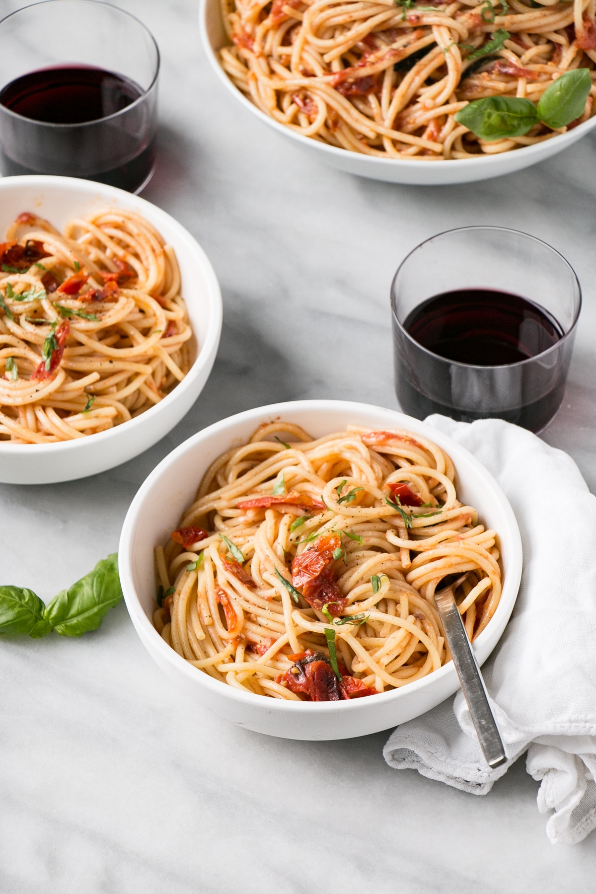Anchovy and Tomato Pasta in a white bowl with red wine and white linen.