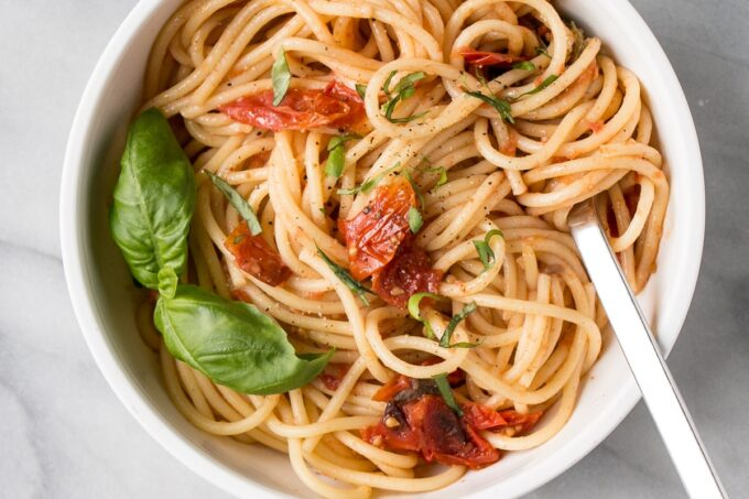 Anchovy and Tomato Pasta in a white bowl.