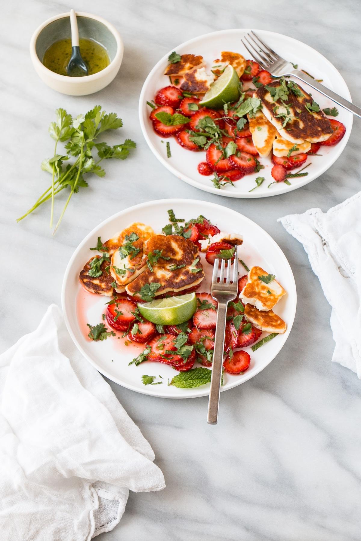 Halloumi and Strawberry Salad on white plates.