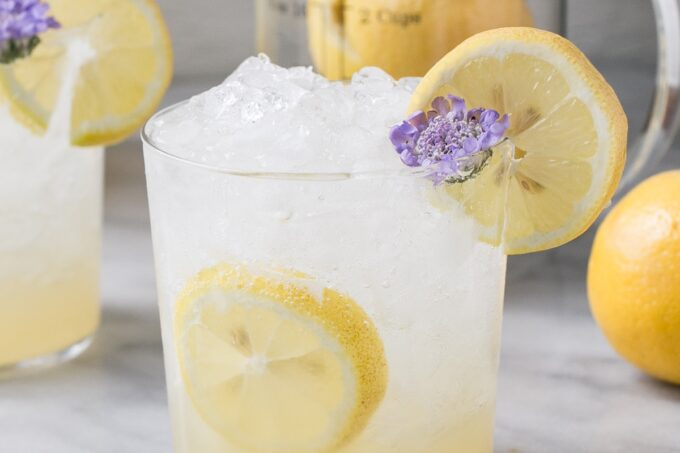 Sugar-Free Lemonade in glasses with lemon slices and a small purple flowers.