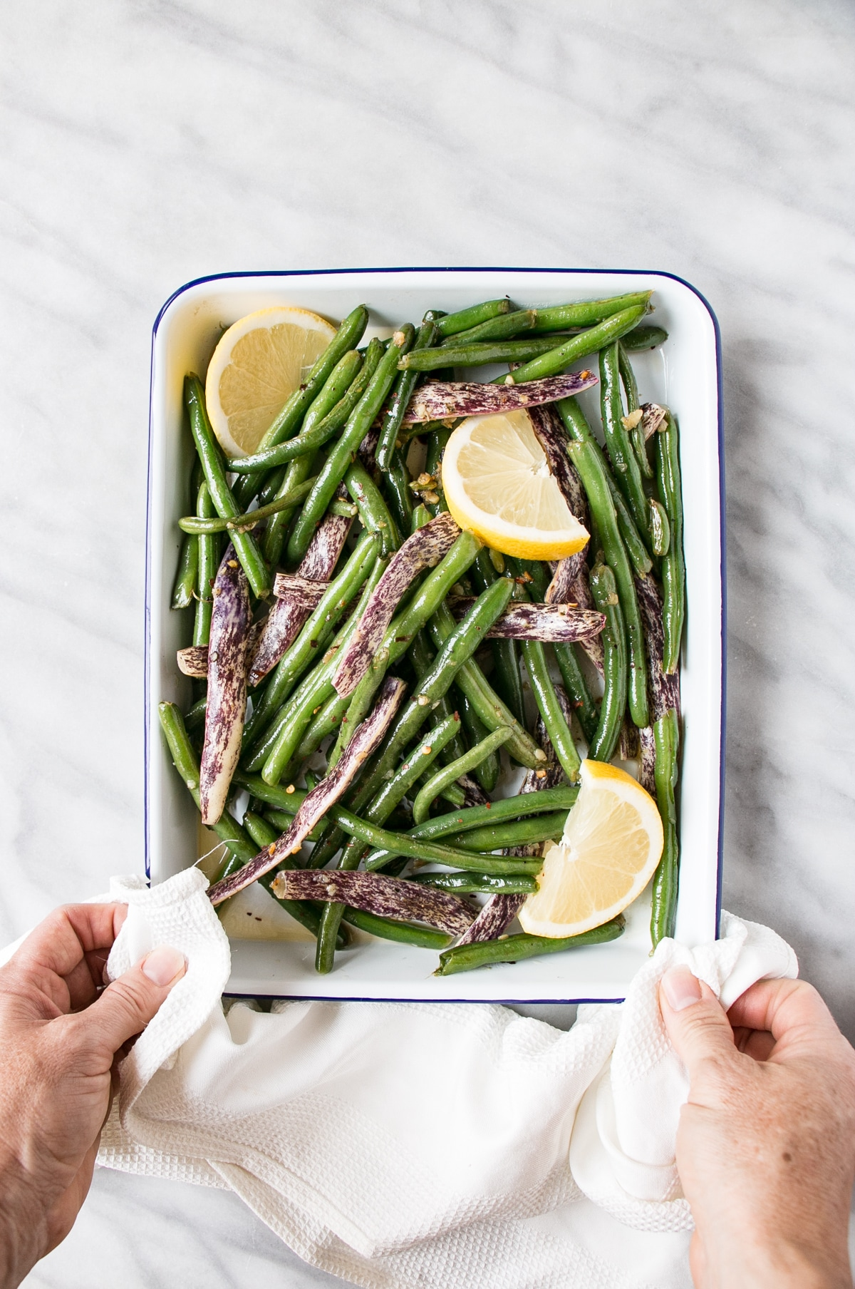 Garlicky Green Beans in a white serving tray being served with someone holding a white dish cloth.