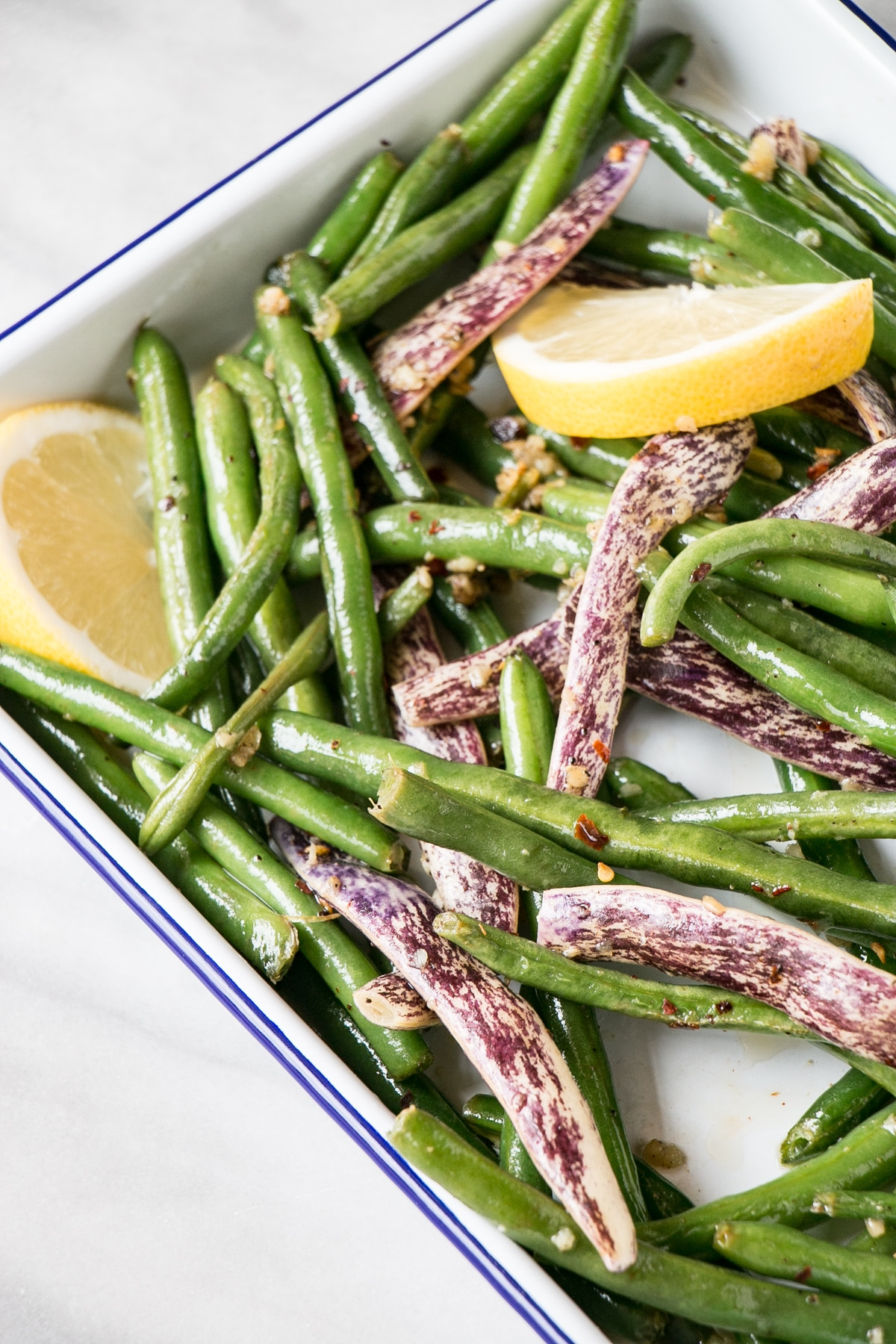 Garlicky Green Beans up close with lemon segements in a white serving tray.