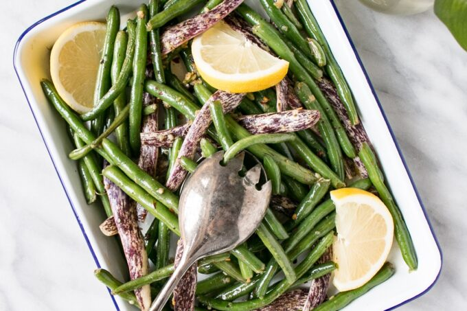 Garlicky Green Beans in a white serving tray with tarnished silver tongs.