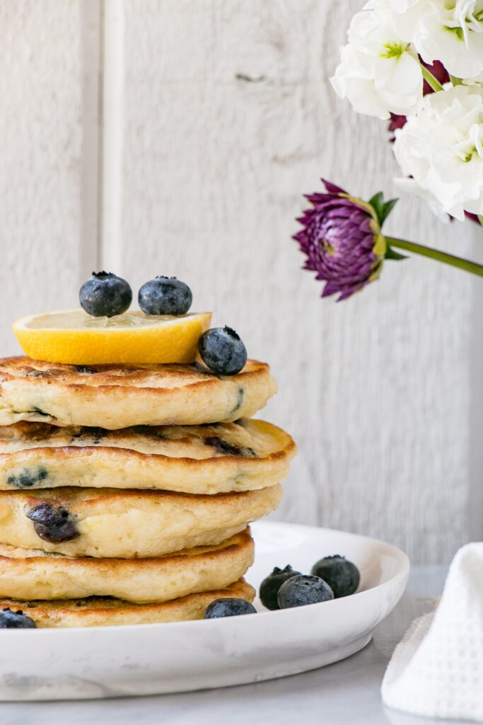 Fluffy Lemon Blueberry Pancakes in a stack with blueberries on a white plate.