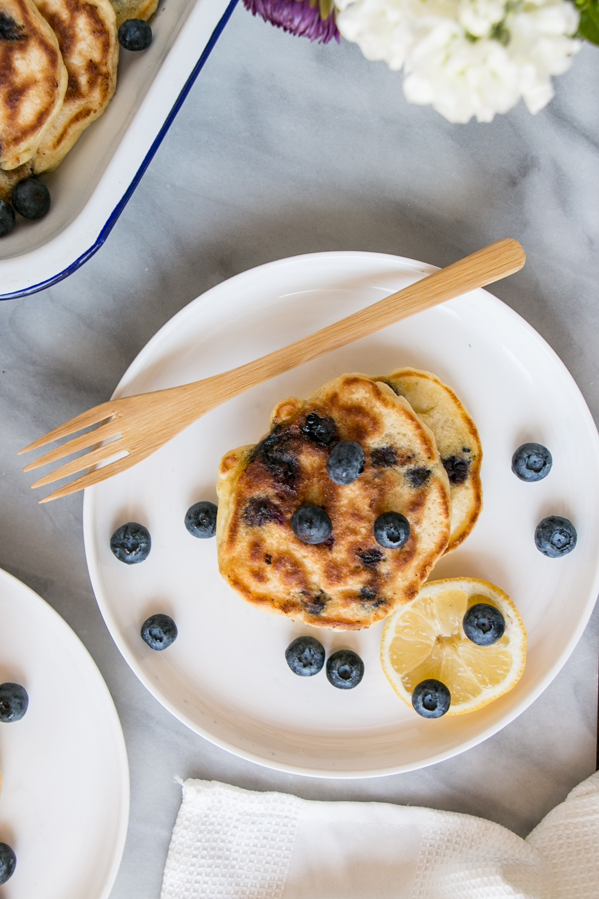 Top down shot of lemon blueberry pancakes with blueberries and a lemon slice on a white plate.