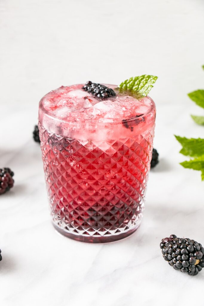 Blackberry Mojito in a textured glass with blackberries, lime and mint.