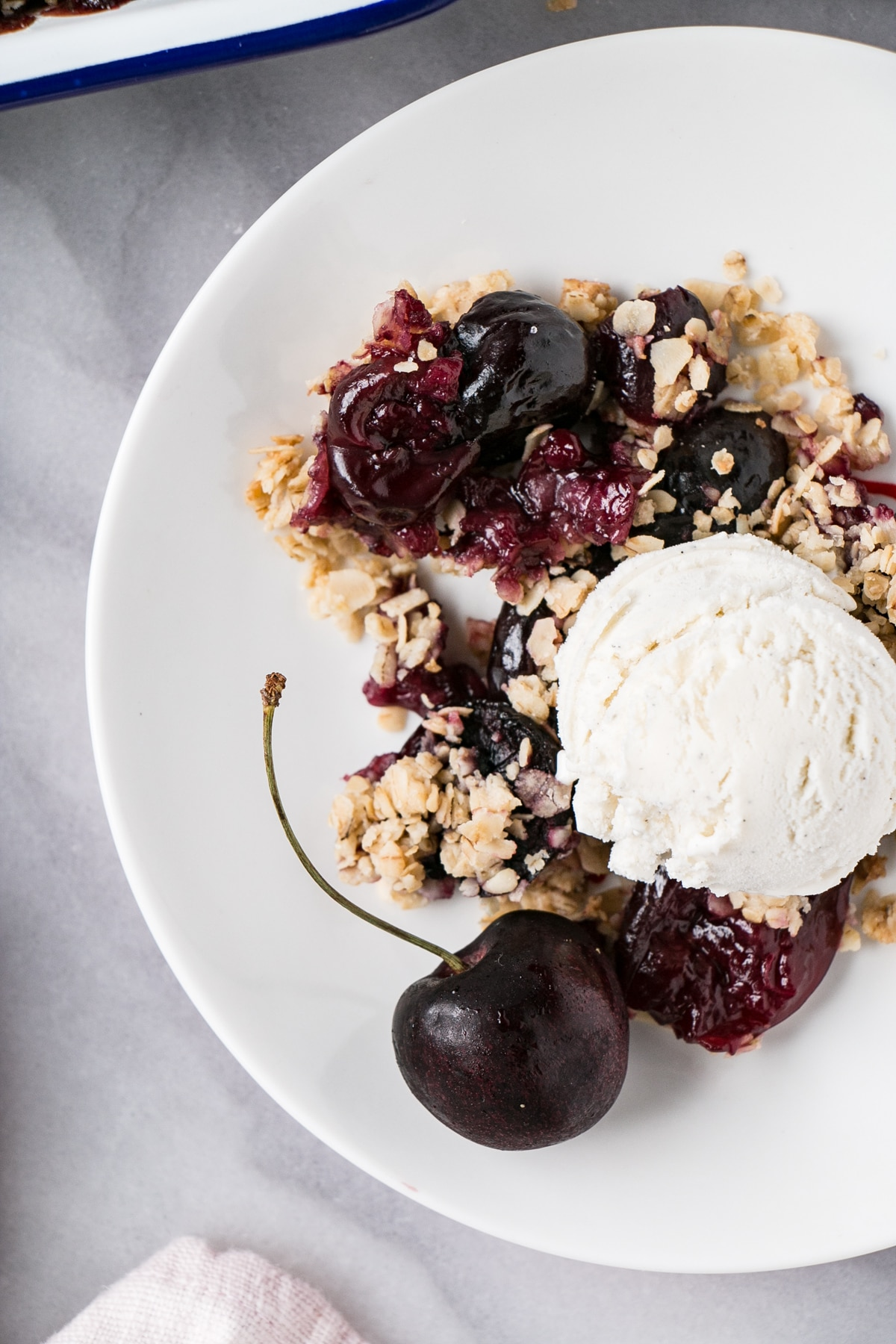 Cherry Crumble on a white plate with a scoop of vanilla ice cream