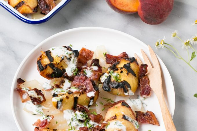 Grilled Peach, Onion and Bacon Salad on a white plate.