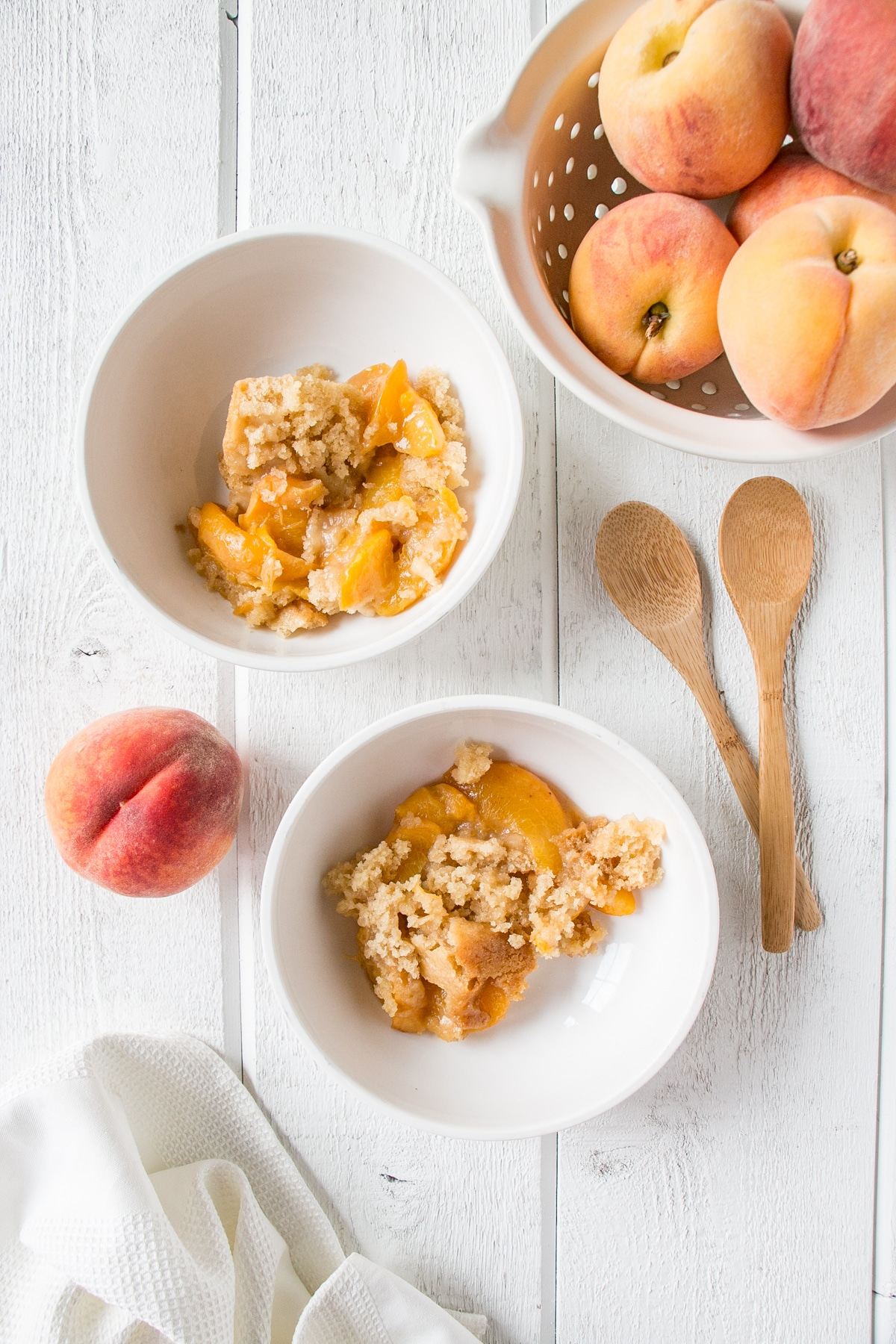 Slow Cooker Peach Cobbler in white bowls