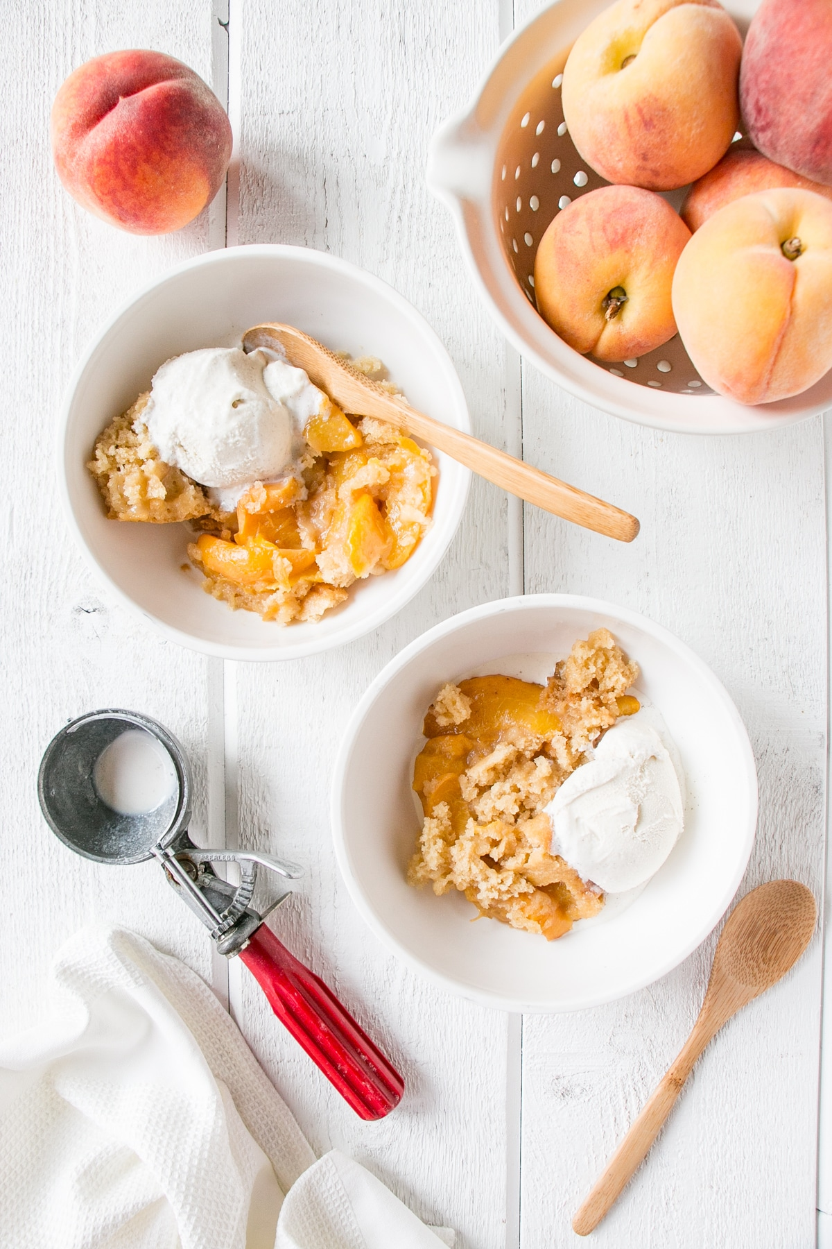 Slow Cooker Peach Cobbler in a white bowl with vanilla ice cream