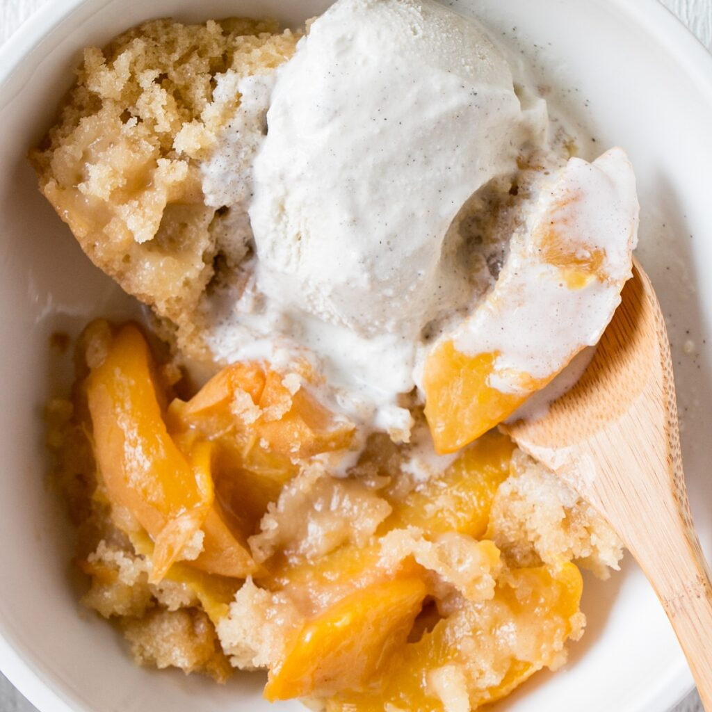 Warm Slow Cooker Peach Cobbler with melting vanilla ice cream.