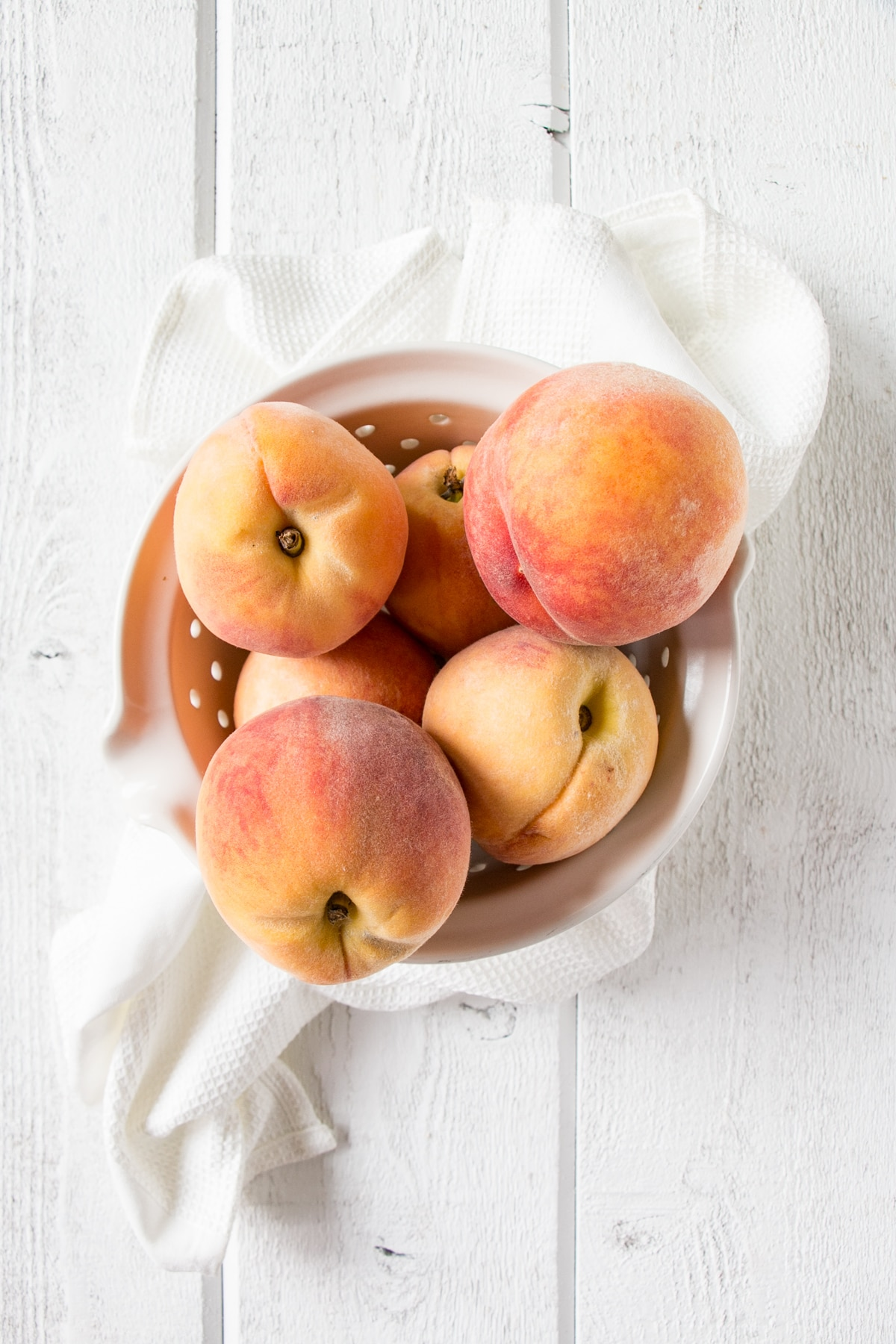 Freestone peaches in a white bowl with a white background.