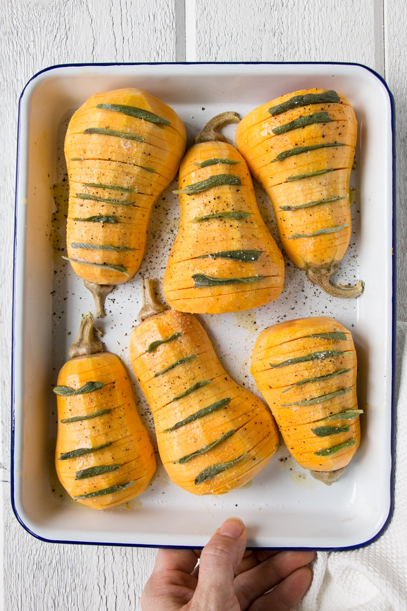 Hassleback Butternut Squash on a white baking tray with sage