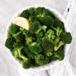 Steamed bright green Broccoli in a white bowl with a slice of fresh lemon.