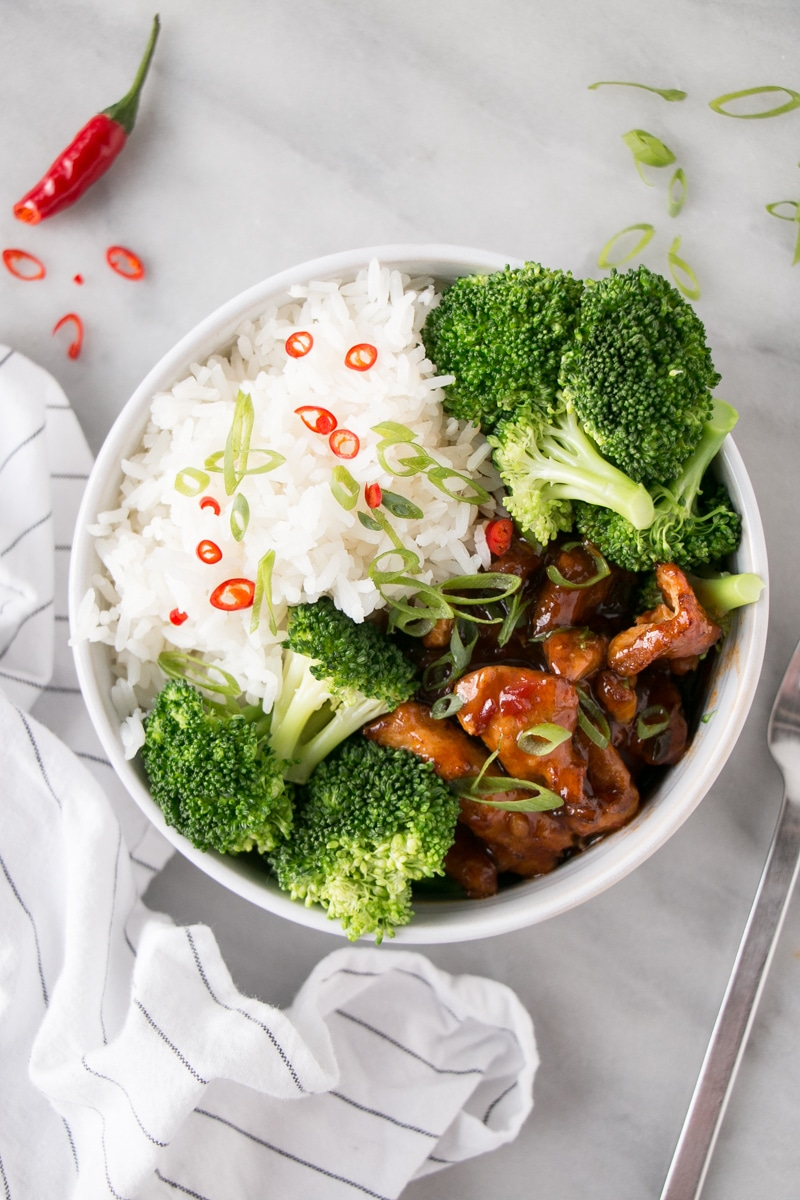 Steamed Broccoli in a shallow bowl with saucy chicken and fluffy white rice.