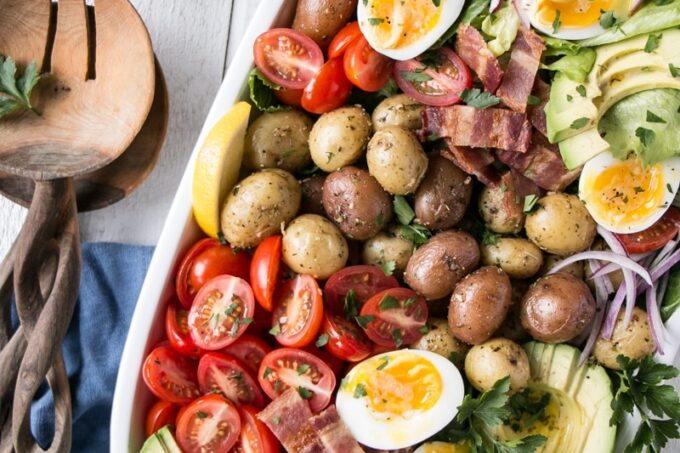 Potato Cobb Salad on a white plate with wooden salad spoons