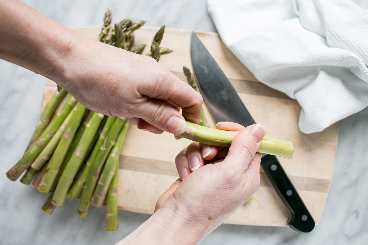 Asparagus being trimmed through a quick break towards the bottom of the vegetable.