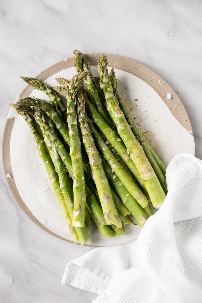Basic how to roast asparagus on a white plate.