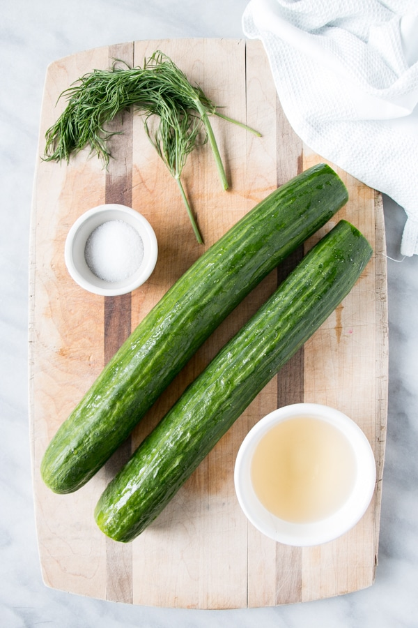 2 cucumbers on a cutting board with dill, vinegar and sugar.