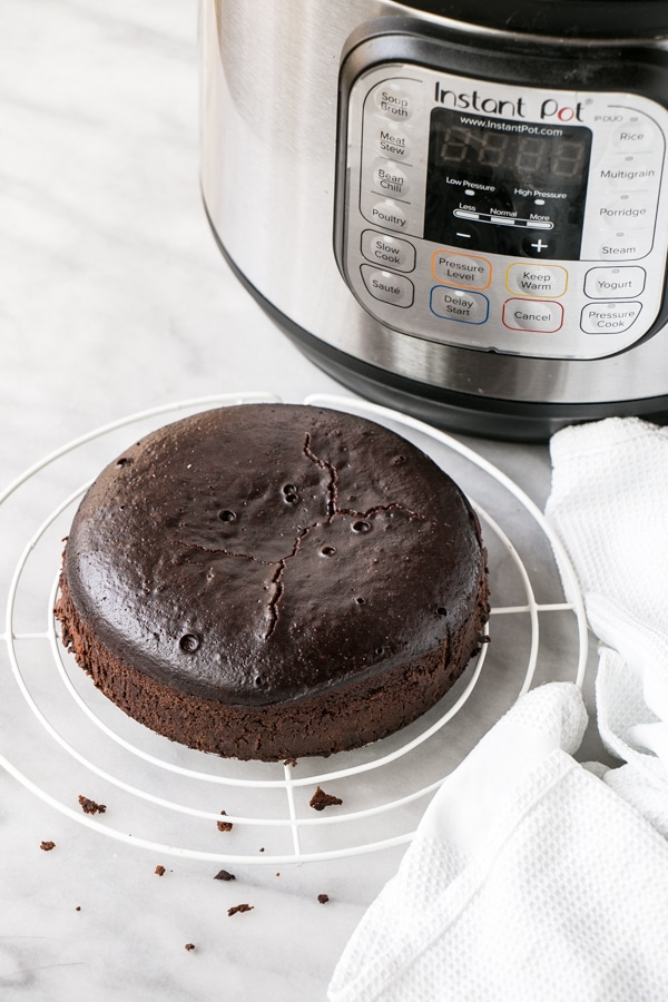 Instant Pot Chocolate Cake on a cooling rack with IP in the background.
