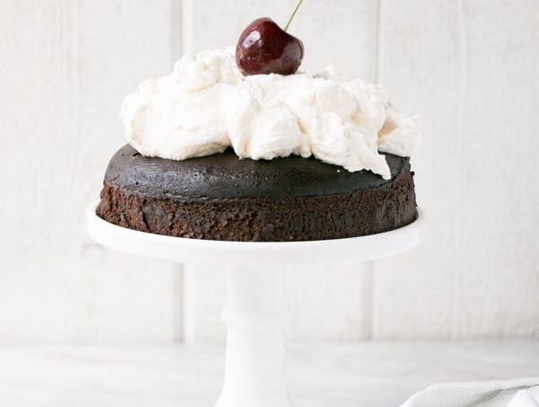 Instant Pot Chocolate Cake with Whipping Cream on a white cake stand.