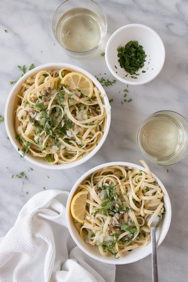 Linguine with Clam Sauce served in white bowls with white wine in short clear cups.
