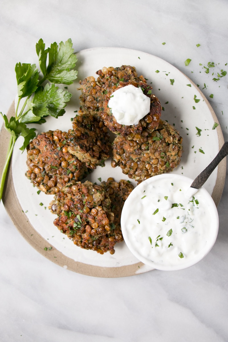 Lentil Patties on a plate with yogurt sauce and parsley leaves.