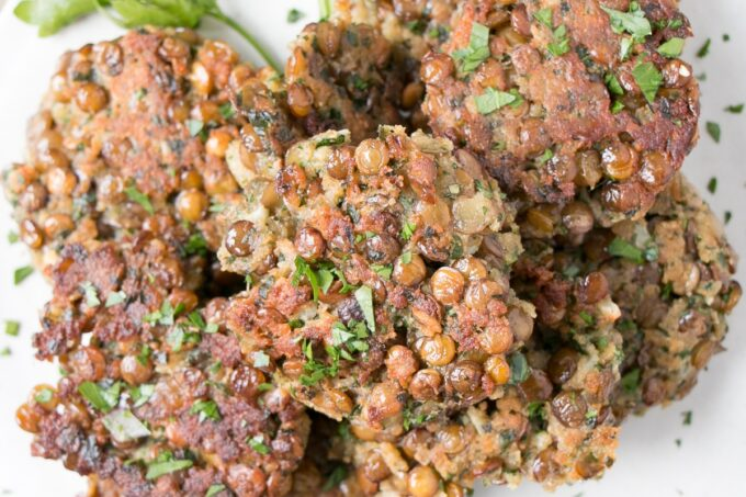 Lentil Fritters piled on a plate with parsley leaves.