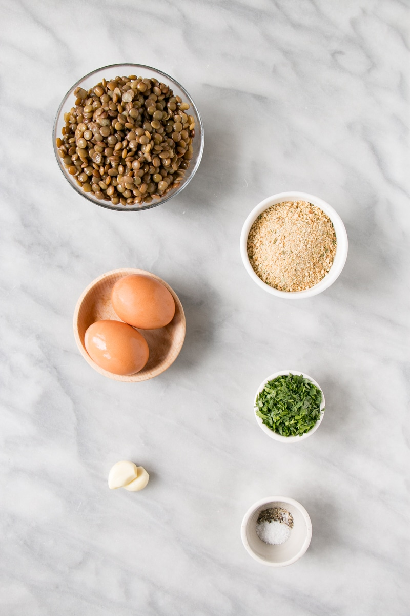 Lentil Patties ingredients on a white marble background.