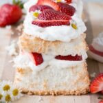 Strawberry Angel Food Cake close up of the end of a loaf angel food cake layered with whipped cream and strawberries.