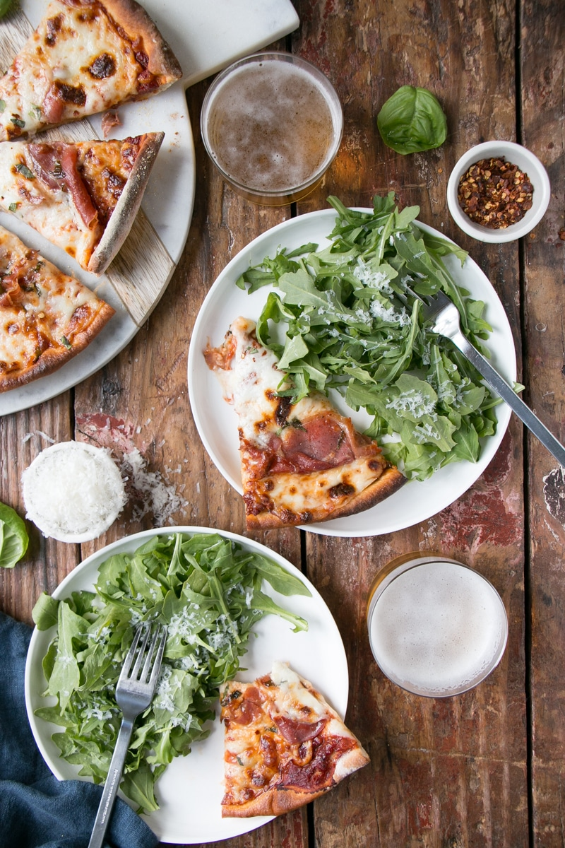 Pizza spread with arugula salad, cold foamy beer, and extra parmesan cheese for garnish.