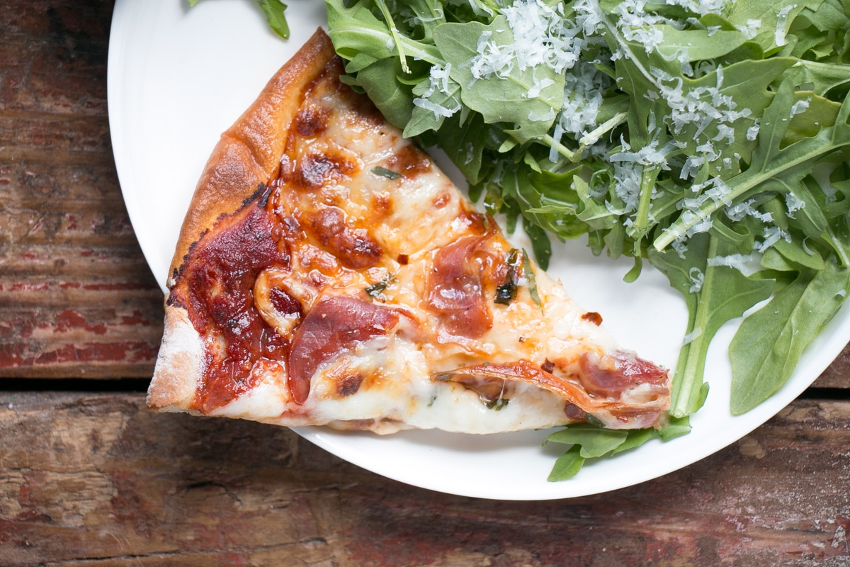 Upclose slice of crispy prosciutto pizza with melty cheese and a side arugula salad.
