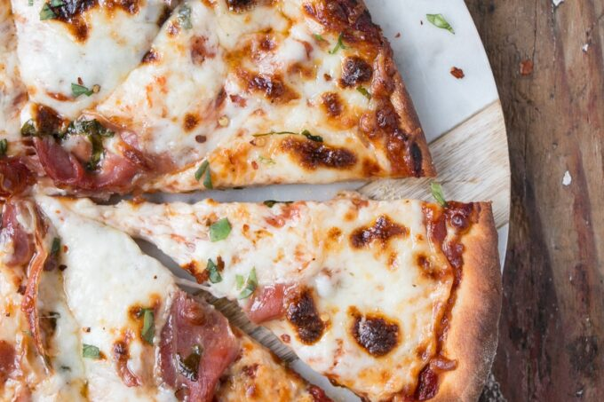 Melty cheese and crispy prosciutto pizza with bits of bright basil.