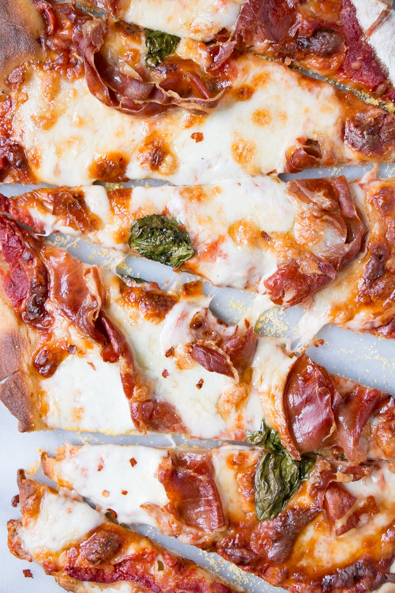 Up close slices of very melty cheese and crispy prosciutto thin crust pizza.