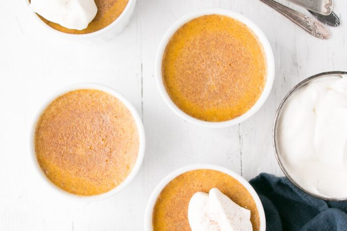Deep golden Pumpkin Egg Custard with a dollop of whipping cream and a light sprinkle of cinnamon.