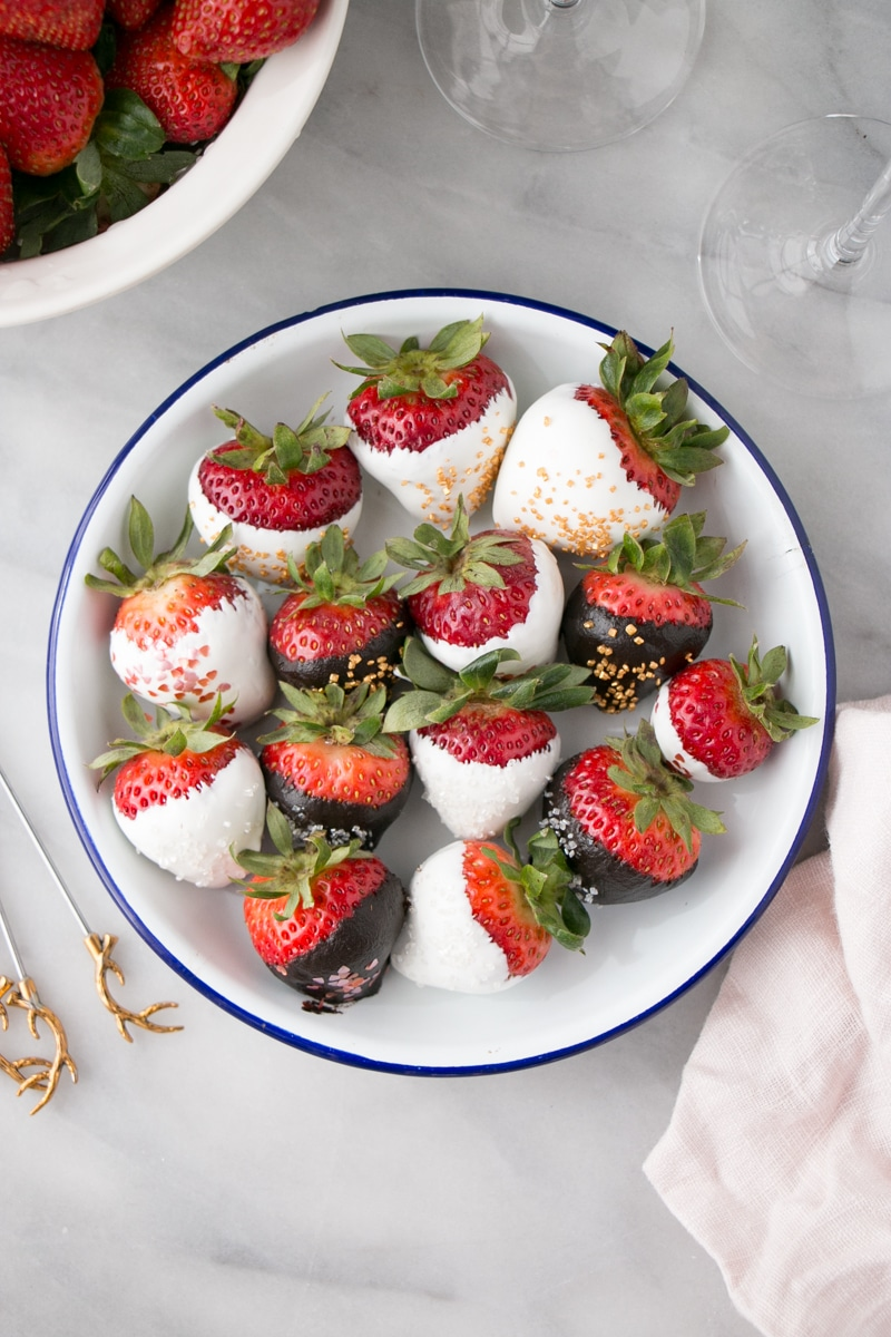 Bright white and dark chocolate covered strawberries with shiny sprinkles as garnish.