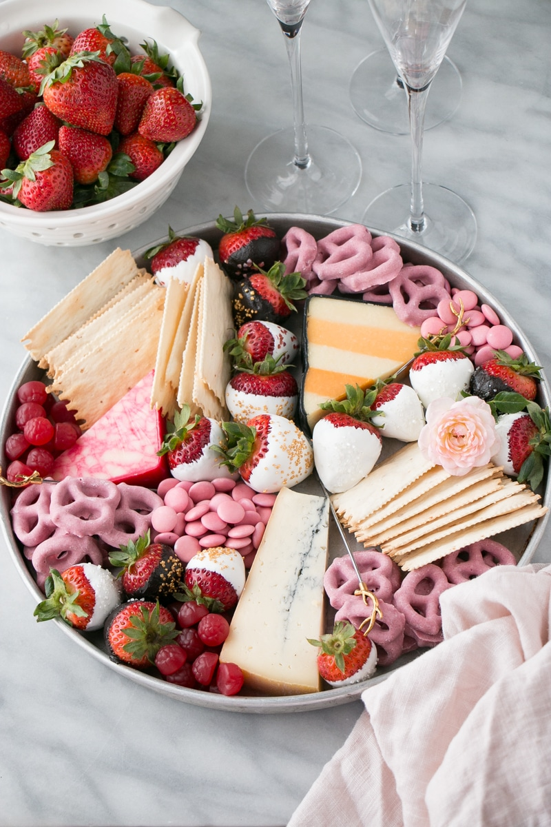 Bright and colourful dessert board with white chocolate and dark chocolate covered strawberries and colourful cheeses.