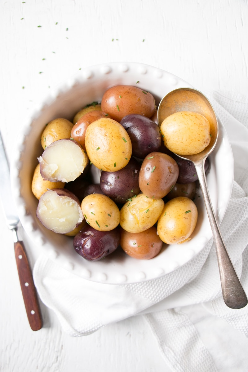 Bright trio coloured boiled potatoes with one cut in half showing a tender fluffy inside.