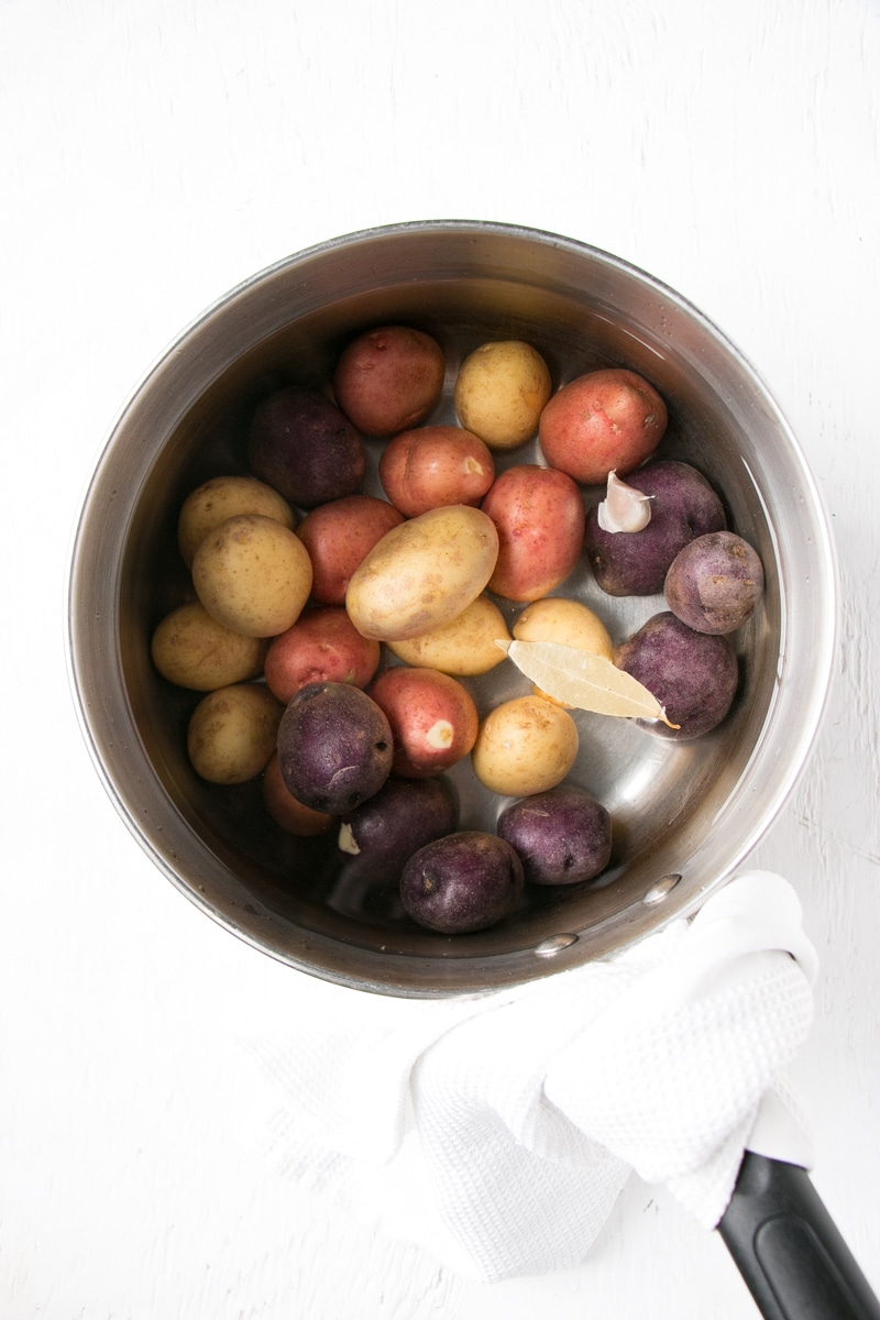 Little potatoes in a sauce pan with flavour boosters, covered in water.