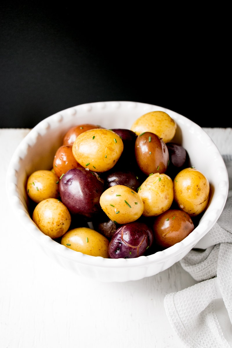 Bright trio coloured boiled potatoes in a white bowl.