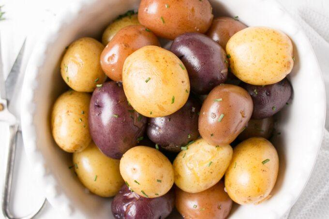 Bright trio coloured boiled potatoes in a white bowl.